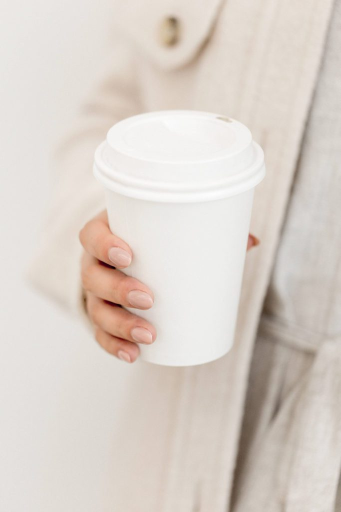 Feminine hands holding a white takeaway coffee cup | influencer rate card