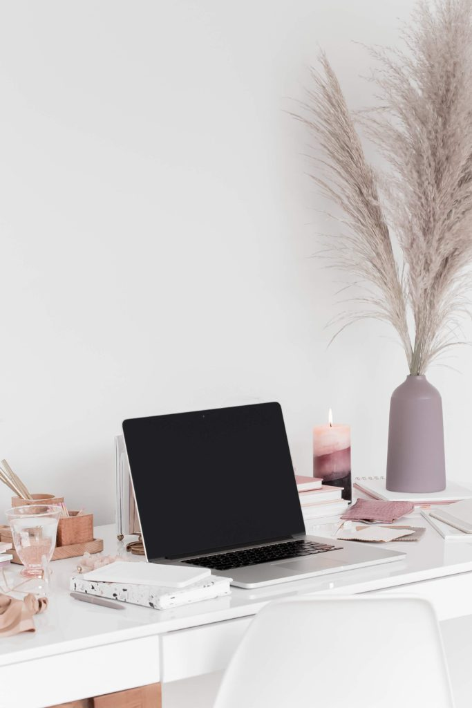 Feminine home office desk with an open laptop and a candle | Learn how to land a brand partnership and get paid as a blogger