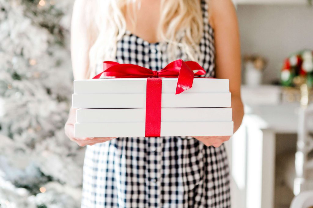 woman holding a big white gift box with red bow | 2020 Christmas Bucket List Ideas