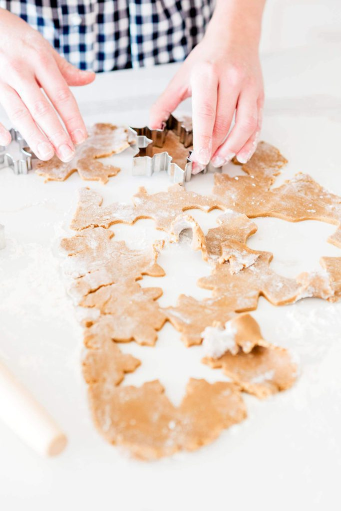 Feminine hands cutting out gingerbread men dough | 2020 Christmas Bucket List ideas