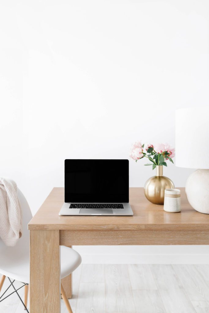 open laptop with a black screen on a desk with a simple vase and flower next to it