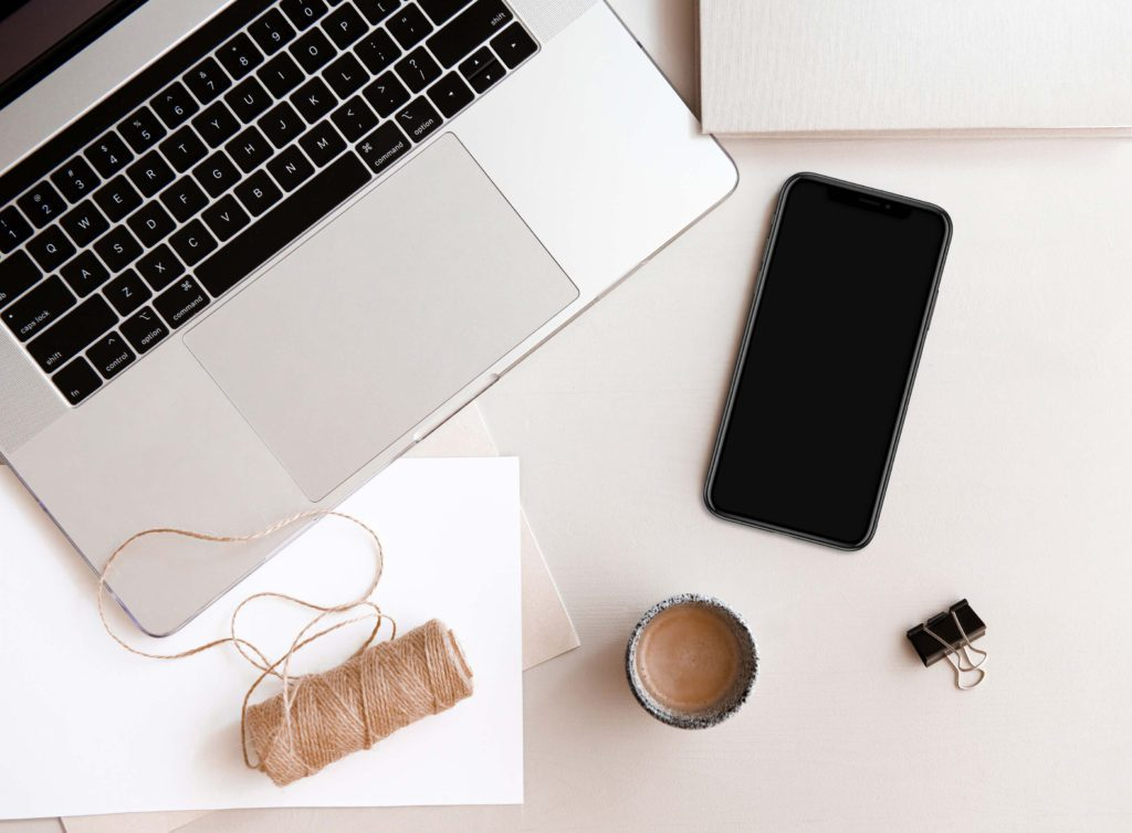 desk flatlay with an apple laptop and a black iphone | best blogging resources