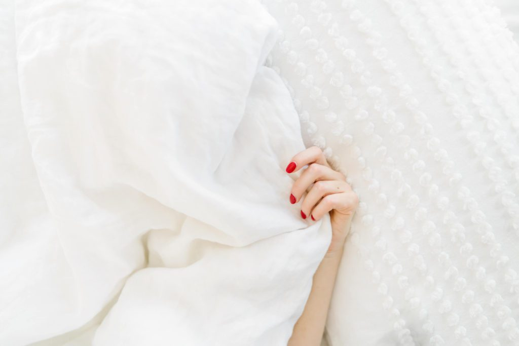 hand with red nail polish under a white blanket | bedtime beauty tips