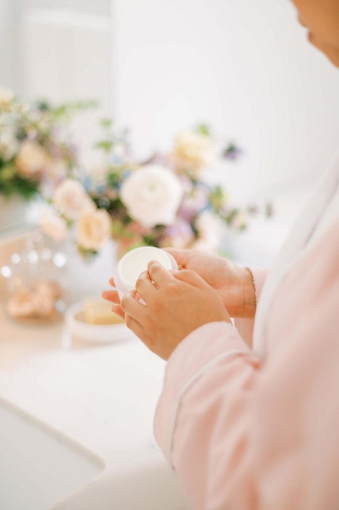 Female hands using cream from a white pot
