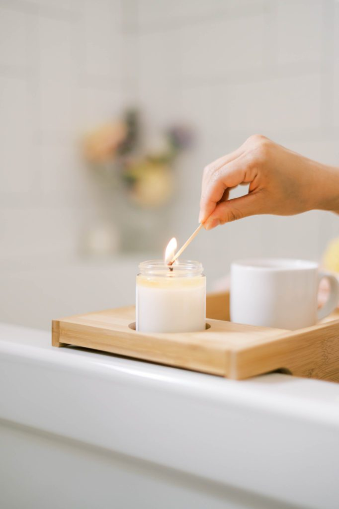 20 Remarkable Benefits of Self-Care | hand lighting candle