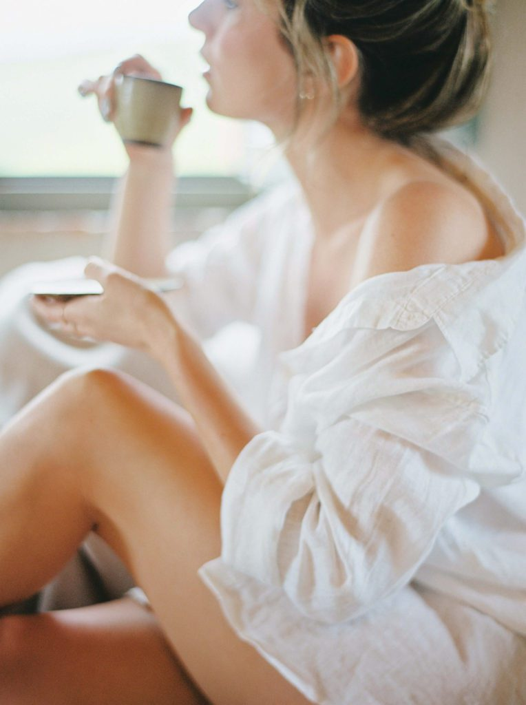 woman wearing a white shirt drinking a cup of coffee