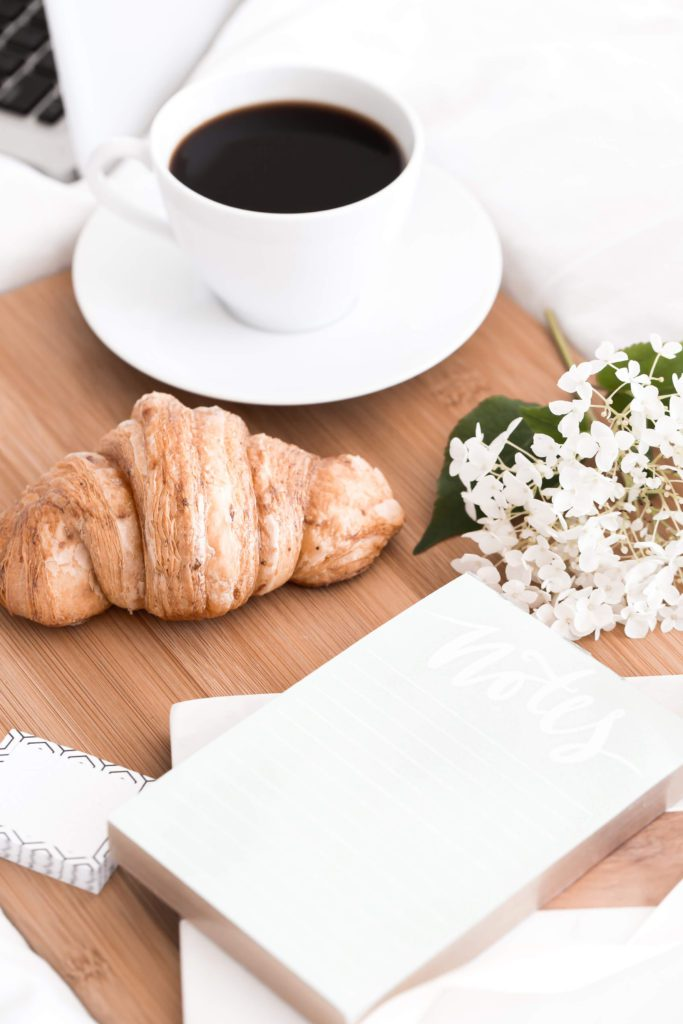 table with a white cup of coffee, a croissant, white flowers and a white book | self care ideas