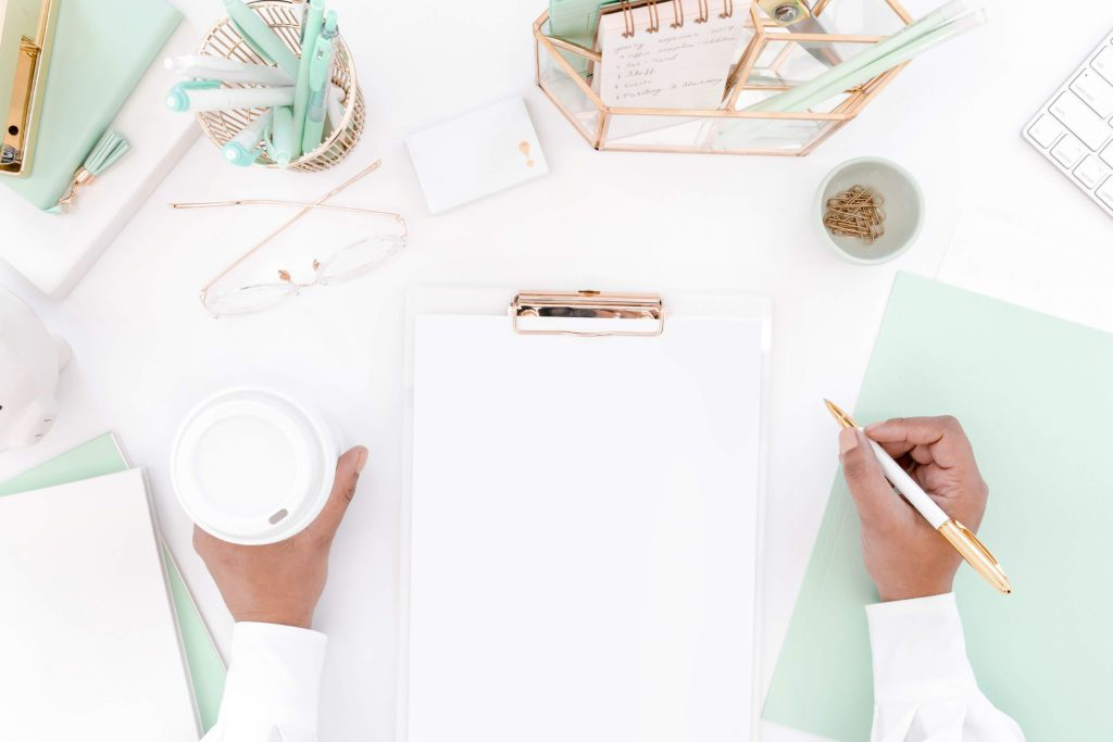 white and mint desk flatlay with hands holding a pen and a coffee
