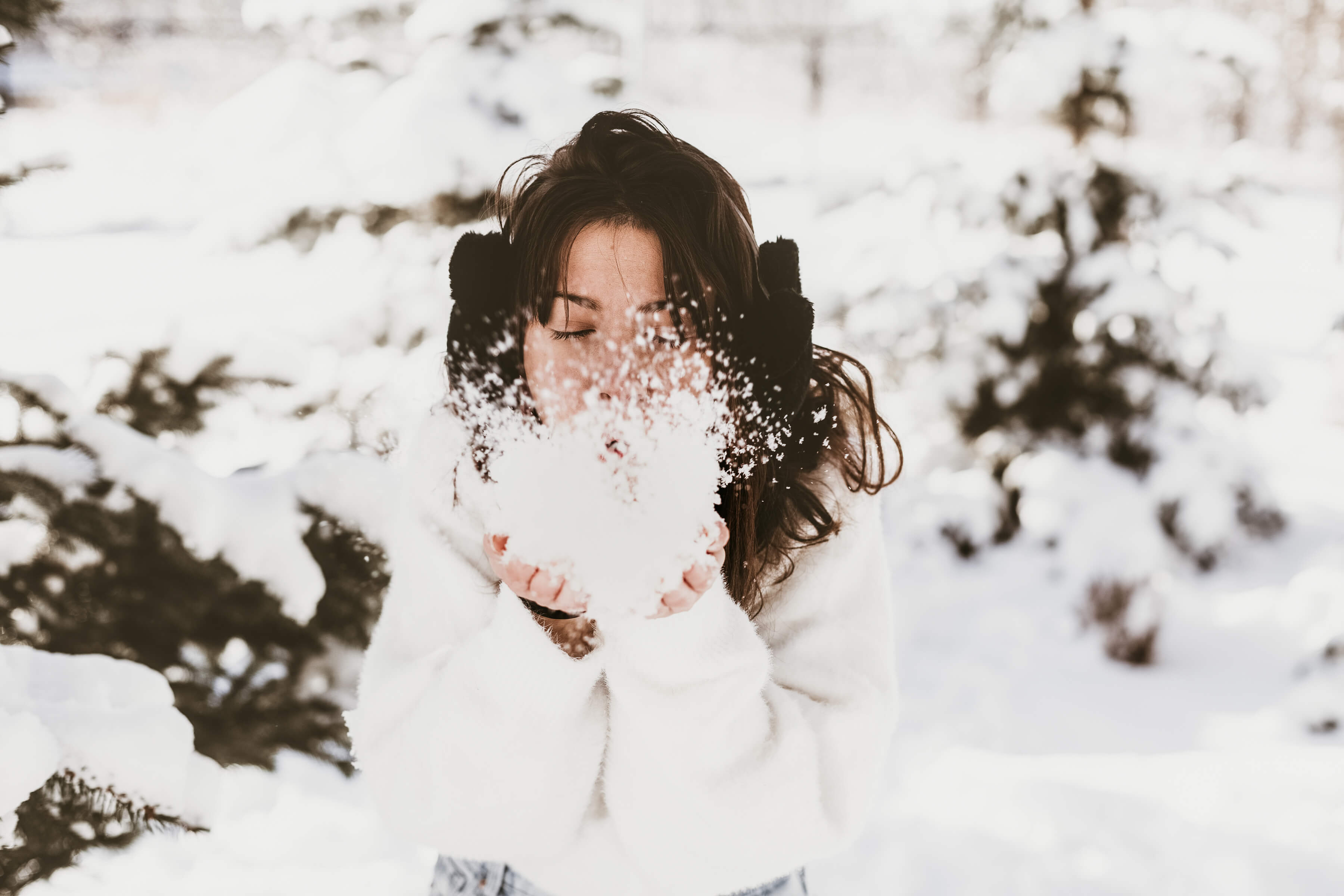 girl blowing snow to the camera. Winter self care ideas & my daily self care routine for cold days
