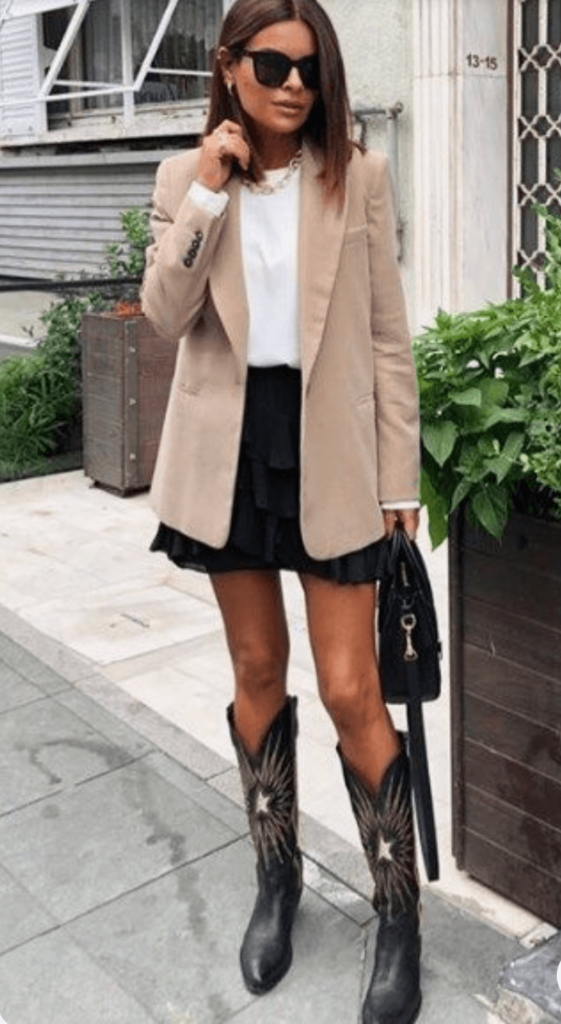 brown cowboy boots with beige blazer and black skirt